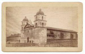 Angle view of old Santa Barbara Mission church; shows twin bell towers, Roman temple facade, stone walls. Two men stand on entrance steps. Santa Barbara; ca. 1887.